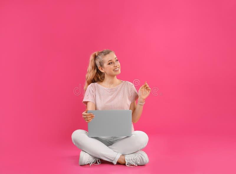 Härlig ung kvinna med bärbara datorn på rosa färger arkivbild