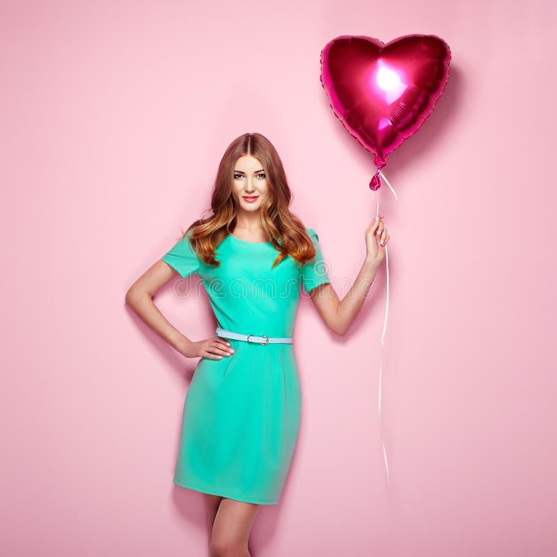 Härlig ung kvinna med ballongen för hjärtaformluft arkivbild