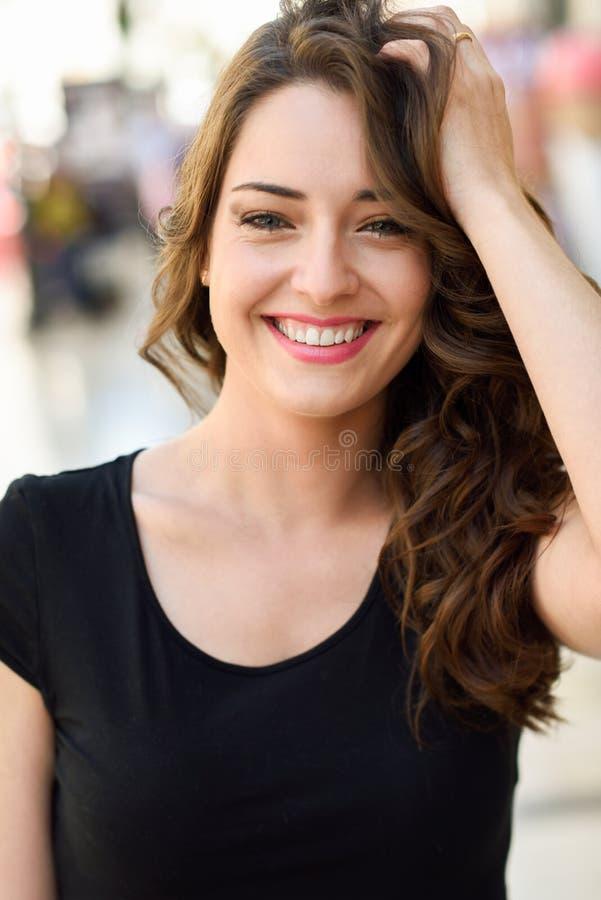Härlig ung kvinna med blåa ögon som ler i stads- bakgrund arkivfoto