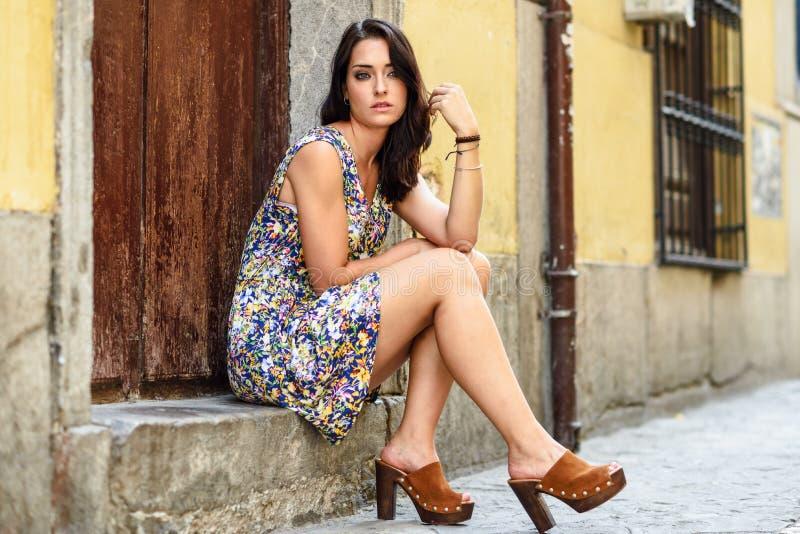 Härlig ung kvinna med blåa ögon som sitter på stads- moment royaltyfri foto
