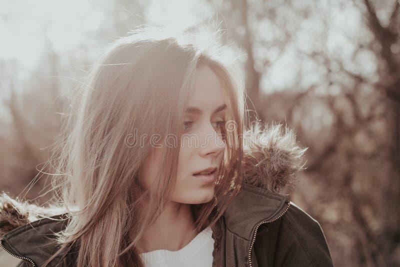 Härlig ung kvinna med blont hår som från sidan ser royaltyfri foto