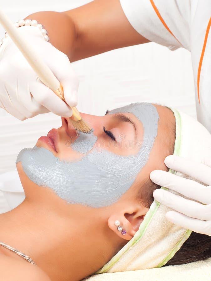 Härlig ung kvinna med den ansikts- maskeringen i skönhetsalong arkivfoto