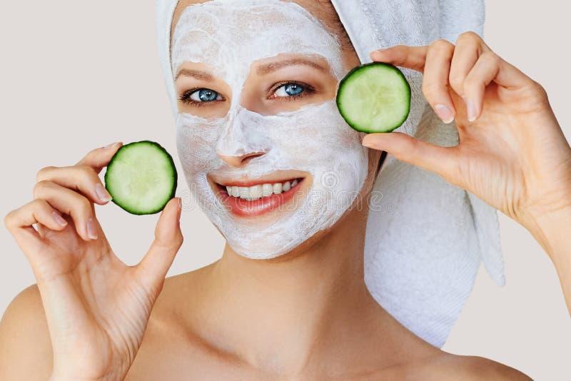 Härlig ung kvinna med den ansikts- maskeringen på hennes framsida som rymmer skivor av gurkan Hudomsorg och behandling, brunnsort royaltyfria foton