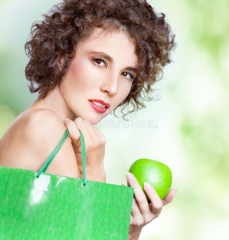 Härlig ung kvinna med den gröna påsen och äpplet royaltyfria bilder