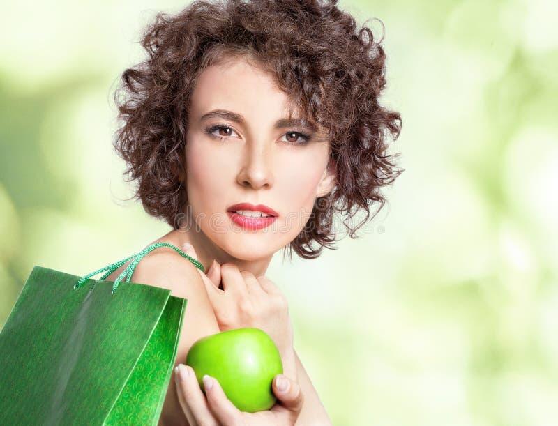 Härlig ung kvinna med den gröna påsen och äpplet royaltyfri fotografi
