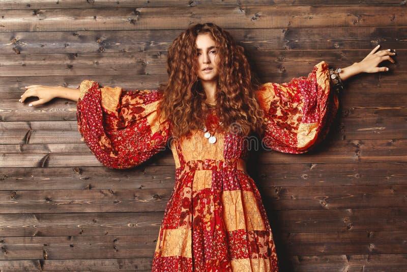 Härlig ung kvinna med den långa lockiga frisyren, modesmycken med brunetthår Indisk stilkläder, lång klänning arkivbilder