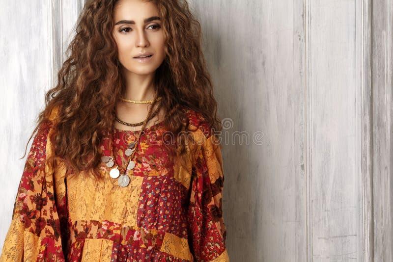 Härlig ung kvinna med den långa lockiga frisyren, modesmycken med brunetthår Indisk stilkläder, lång klänning arkivfoto