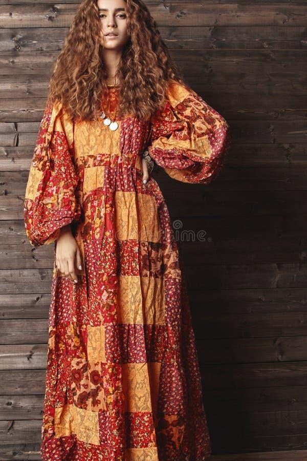 Härlig ung kvinna med den långa lockiga frisyren, modesmycken med brunetthår Indisk stilkläder, lång klänning royaltyfri bild