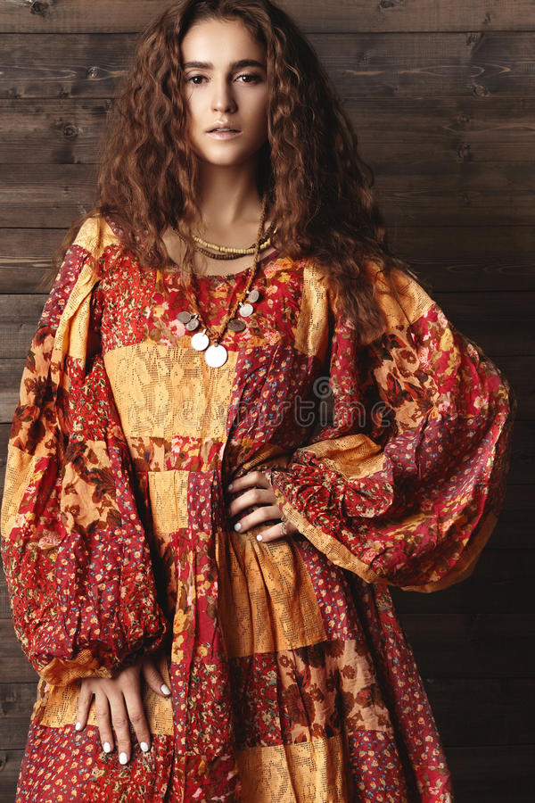 Härlig ung kvinna med den långa lockiga frisyren, modesmycken med brunetthår Indisk stilkläder, lång klänning arkivfoton