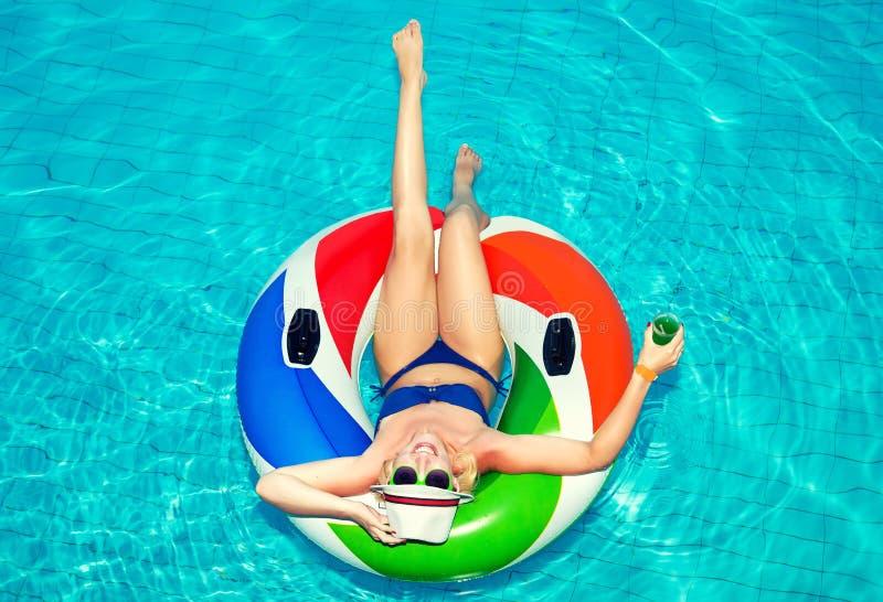 Härlig ung kvinna med den uppblåsbara cirkeln som kopplar av i blåa simbassäng och drinkar en coctail royaltyfri bild