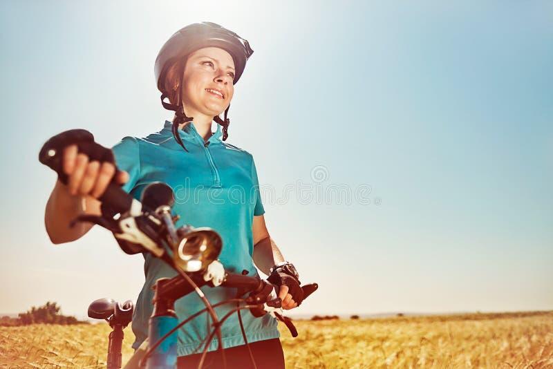 Härlig ung kvinna med en cykel på ett fält royaltyfria foton