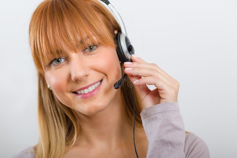 Härlig ung kvinna med en hörlurar med mikrofon fotografering för bildbyråer