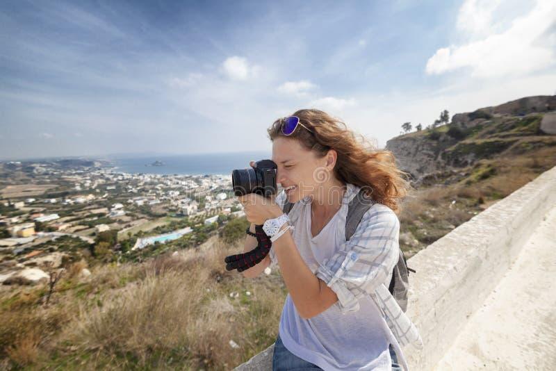 Härlig ung kvinna med en kamera i hand, handelsresande och blogge arkivbild