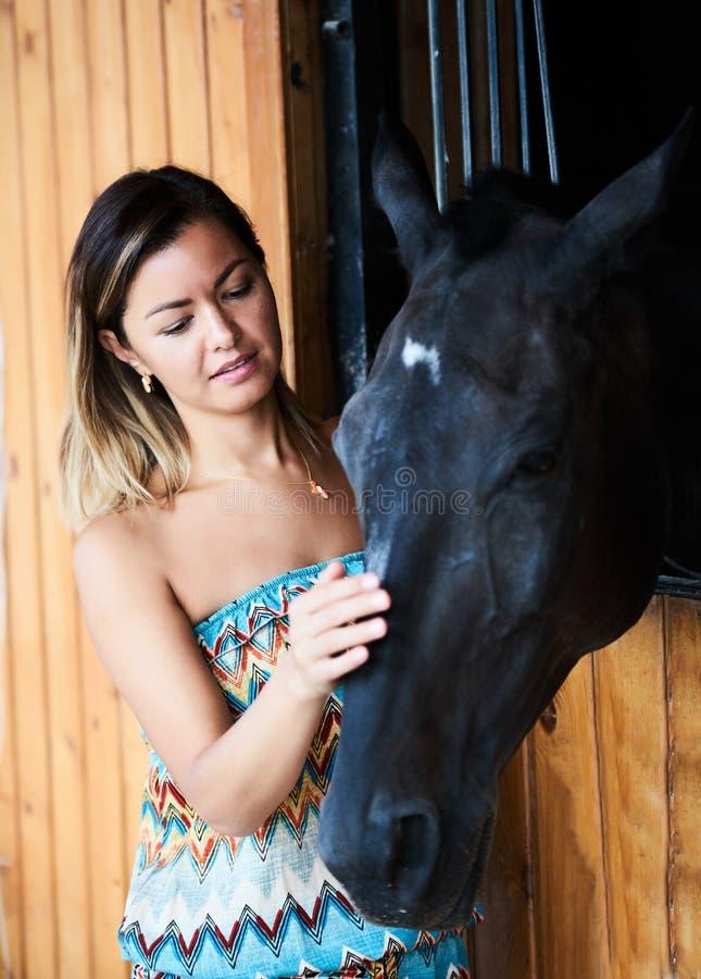 Härlig ung kvinna med en kastanjebrun häst arkivfoton
