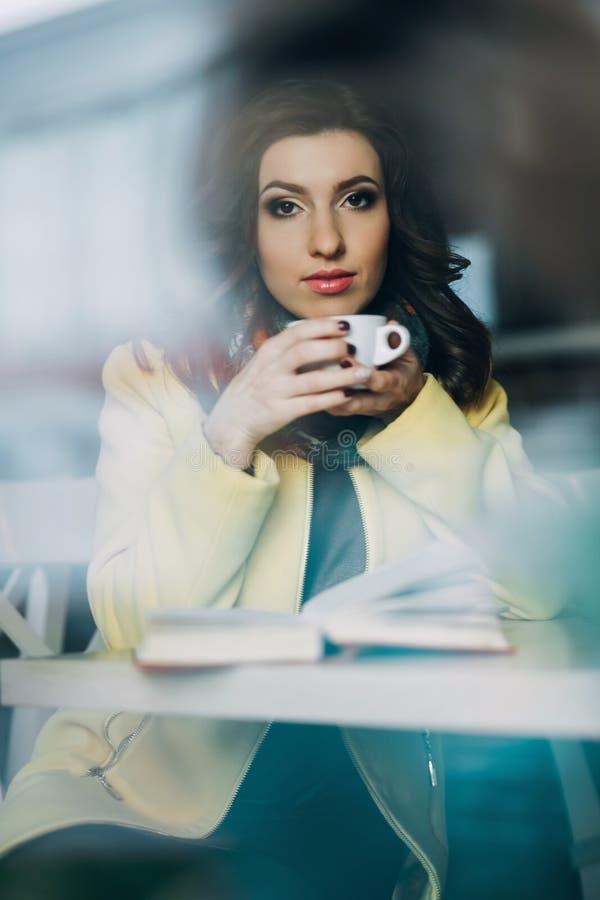 Härlig ung kvinna med en kopp te eller ett kaffe arkivfoto