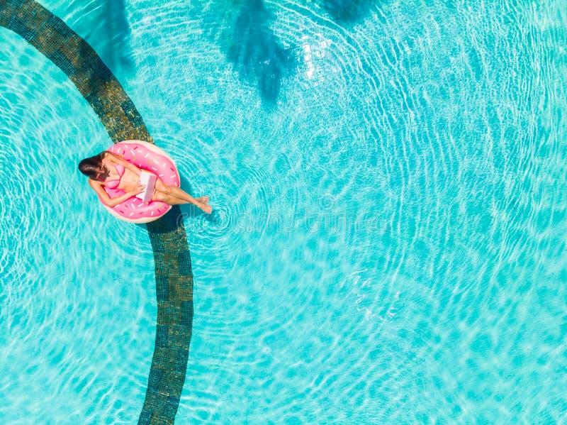 Härlig ung kvinna med en rosa bärbar dator på en uppblåsbar cirkel i vattnet i simbassängen frilansa affär arkivbild