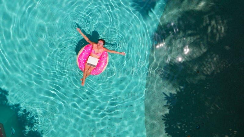 Härlig ung kvinna med en rosa bärbar dator på en uppblåsbar cirkel i vattnet i simbassängen frilansa affär royaltyfri foto