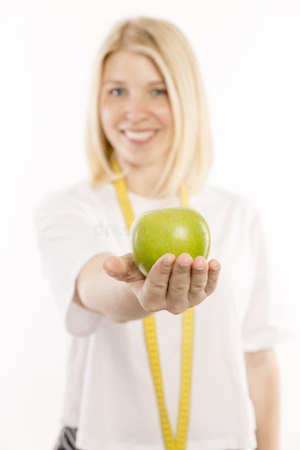 Härlig ung kvinna med ett grönt äpple i hennes le för hand royaltyfria foton