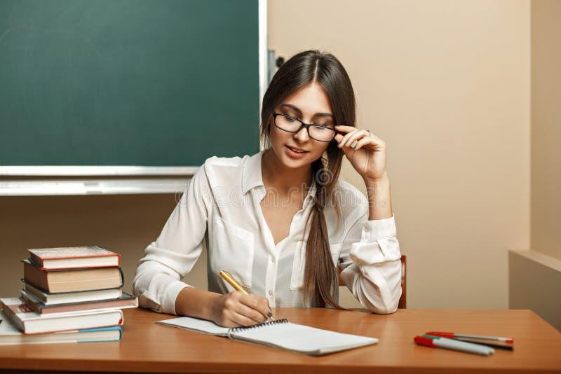 Härlig ung kvinna med exponeringsglas som ska studeras på universitetet royaltyfri bild