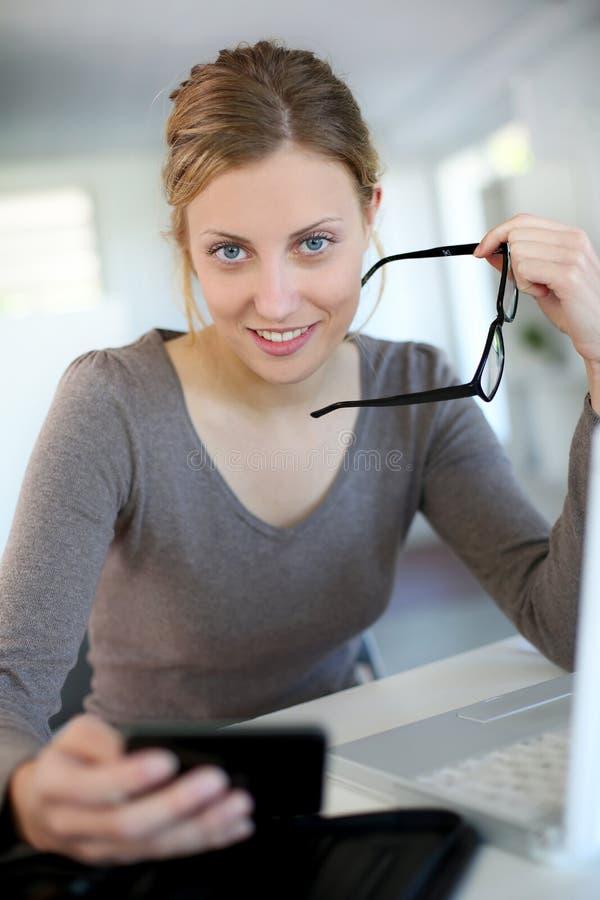 Härlig ung kvinna med glasögon som hemma studerar royaltyfria foton