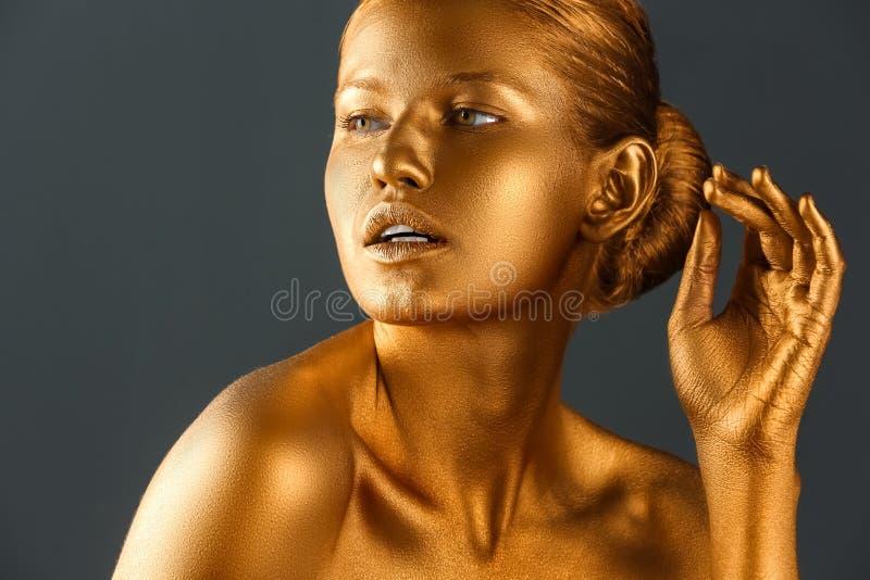 Härlig ung kvinna med guld- målarfärg arkivbild