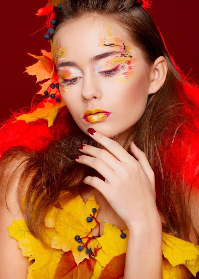 Härlig ung kvinna med höstsminket som över poserar i studio royaltyfri bild
