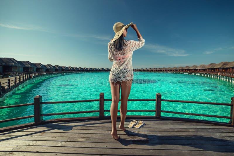 Härlig ung kvinna med hatten på den vita stranden, härligt landskap med kvinnan i Maldiverna, tropiskt paradis arkivbilder