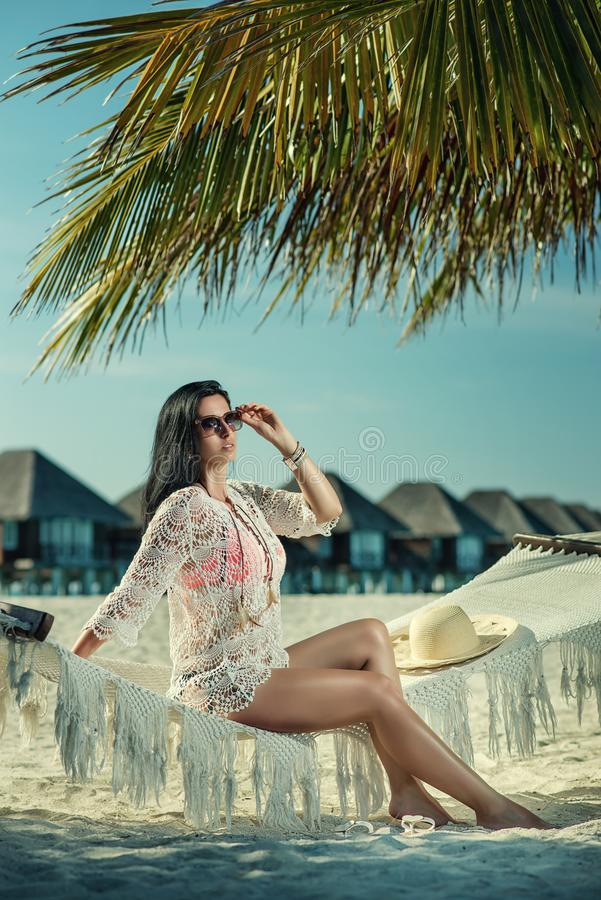 Härlig ung kvinna med hatten på den vita stranden, härligt landskap med kvinnan i Maldiverna, tropiskt paradis arkivfoton