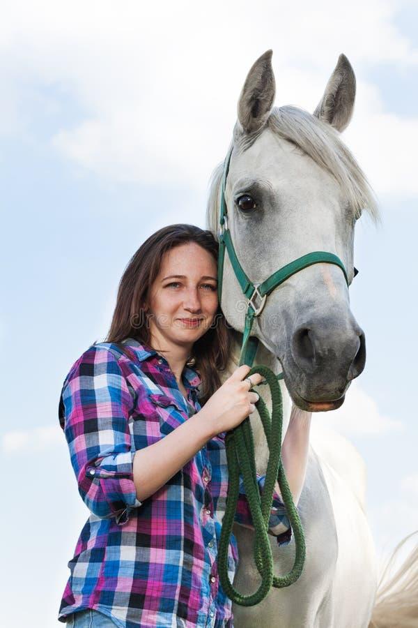Härlig ung kvinna med hennes älskvärda vita häst arkivbild