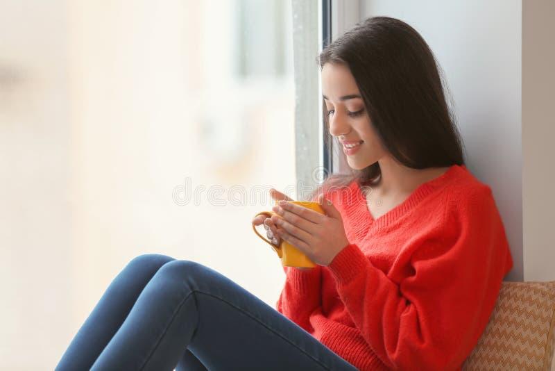 Härlig ung kvinna med koppen av varmt te som hemma sitter på fönsterbräda fotografering för bildbyråer