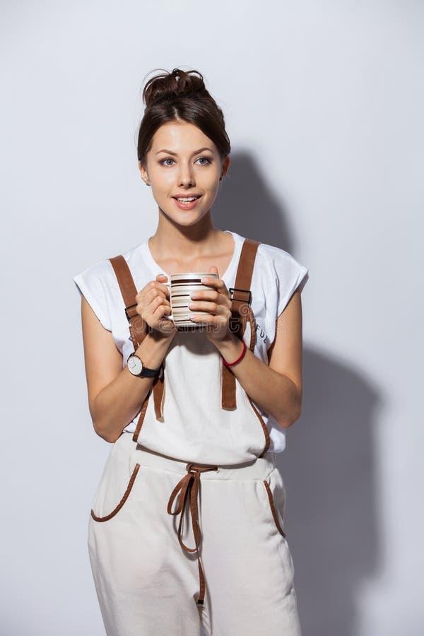 Härlig ung kvinna med koppen kaffe som isoleras på vit arkivfoto