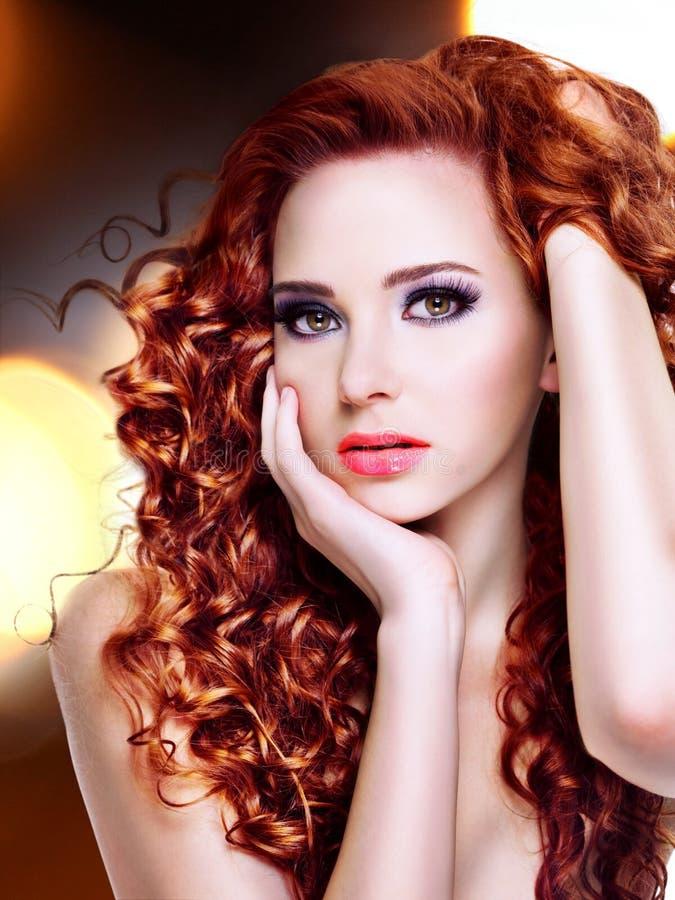 Härlig ung kvinna med långa lockiga hår royaltyfria foton