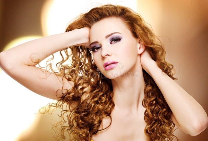 Härlig ung kvinna med långa lockiga hår arkivbilder