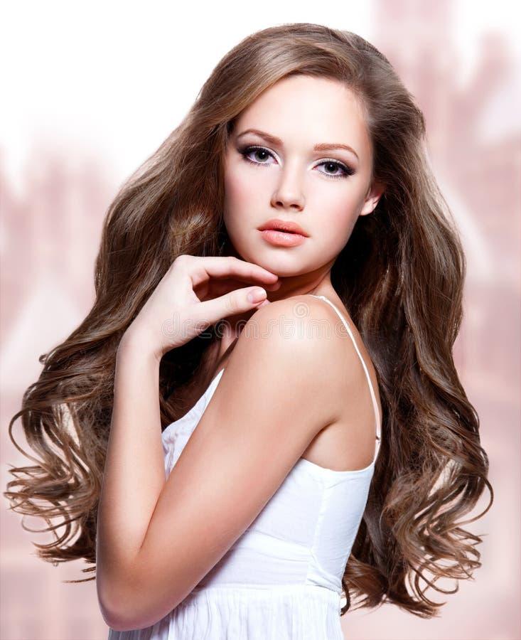 Härlig ung kvinna med långa lockiga hår royaltyfri foto