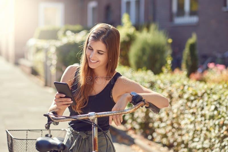 Härlig ung kvinna med långt hår i i halvfigur främre stående utomhus i stadsanseendet som lutar på att använda för tappningcykel arkivfoton