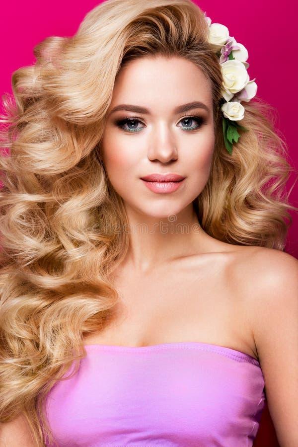 Härlig ung kvinna med långt hår som poserar på rosa skinande bakgrund royaltyfri bild