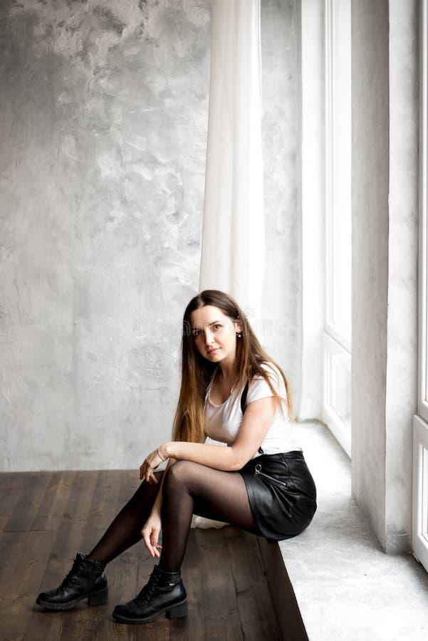 Härlig ung kvinna med långt hår som sitter på fönsterfönsterbräda i rum med turkosväggen Hon är se och tycka om tid arkivfoto