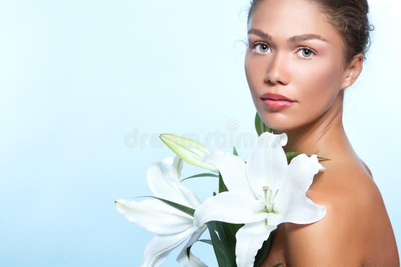 Härlig ung kvinna med med liljablommor, kvinnlig framsida och sh royaltyfri bild