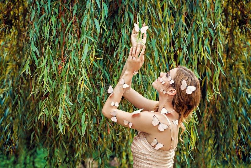 Härlig ung kvinna med många fjärilar royaltyfri foto