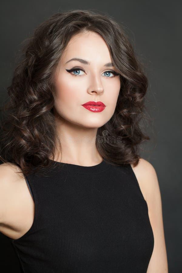 Härlig ung kvinna med makeup och closeupståenden för lockigt hår arkivbilder