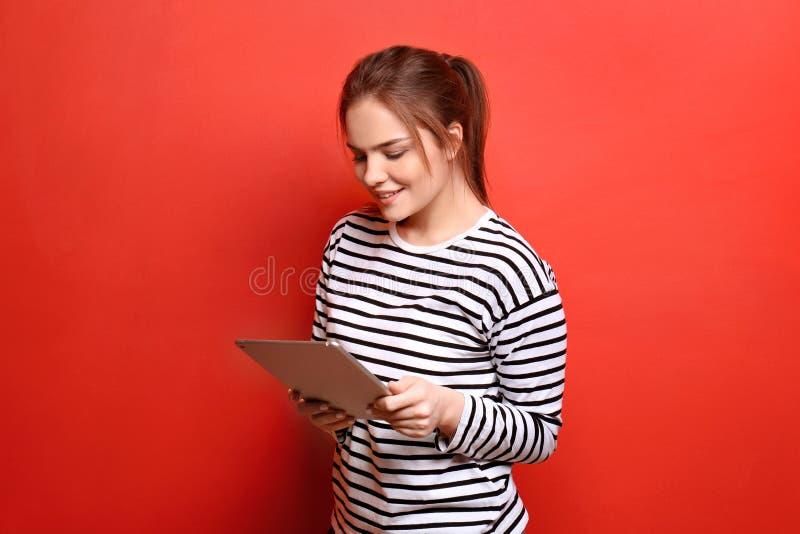 Härlig ung kvinna med minnestavlaPC på färgbakgrund royaltyfri bild