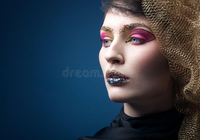 Härlig ung kvinna med modemakeup som isoleras på blått royaltyfri foto