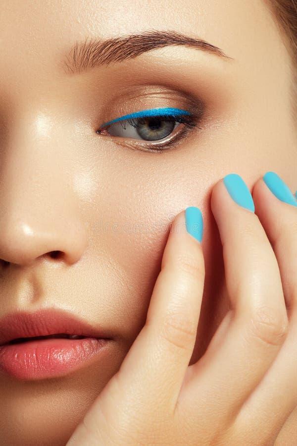Härlig ung kvinna med moderiktig blå makeup pärlor för blå för begrepp för bakgrundsskönhet blir grund naturliga over för behålla royaltyfri bild