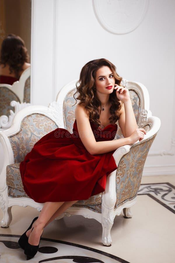Härlig ung kvinna med perfekt smink- och hårstil i ursnygg röd aftonklänning i dyr lyxig inre fotografering för bildbyråer