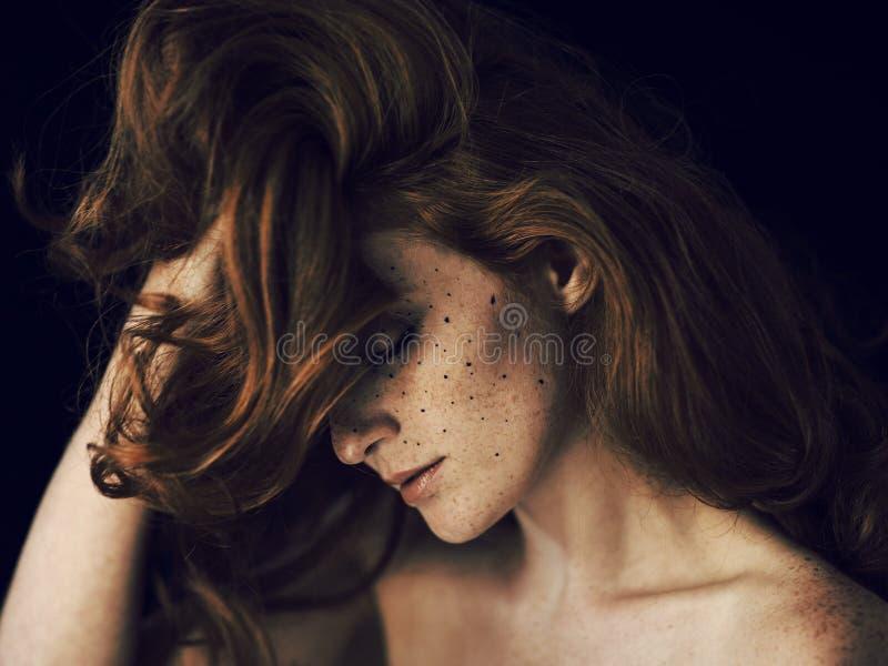Härlig ung kvinna med rött hår och fräknar stående, skönhetfors på mörk bakgrund fotografering för bildbyråer