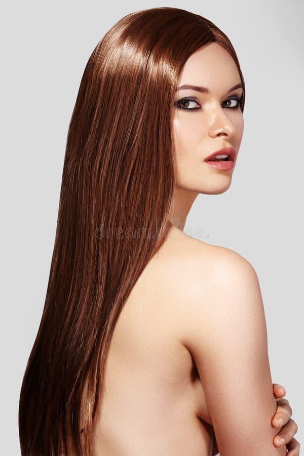 Härlig ung kvinna med ren hud, rakt skinande hår, modemakeup Sexig brunett för stående med den släta frisyren royaltyfri foto