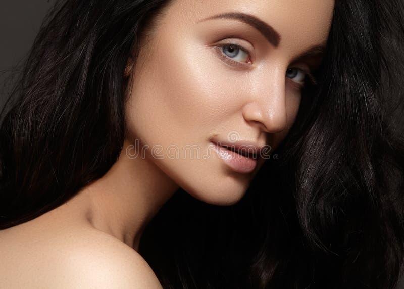 Härlig ung kvinna med ren hud, skinande hår, modemakeup Glamoursminket, gör perfekt formögonbryn arkivfoto