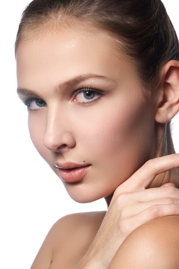 Härlig ung kvinna med ren ny hud Stående av den härliga unga flickan med ren hud på den nätta framsidan - vit bakgrund royaltyfri foto