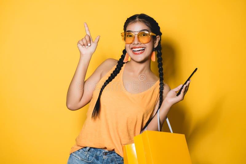 Härlig ung kvinna med shoppingpåsar genom att använda hennes smarta telefon arkivfoton