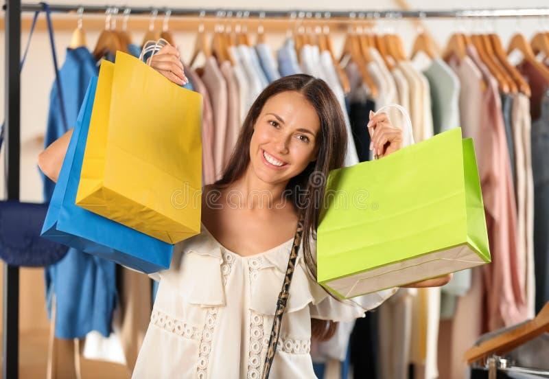 Härlig ung kvinna med shoppingpåsar i klädlager royaltyfri foto